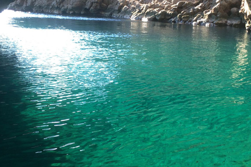 "the mystical ""Gangara Hollow,"" a cave filled with cobalt blue waters"